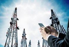 Geschäftsmann unter Verwendung des Handys mit Telekommunikation ragt mit Fernsehantennen und -Satellitenschüssel hoch lizenzfreies stockbild