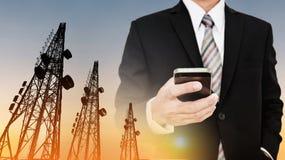 Geschäftsmann unter Verwendung des Handys mit Telekommunikation ragt mit Fernsehantennen und -Satellitenschüssel im Sonnenunterga lizenzfreies stockfoto