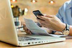 Geschäftsmann unter Verwendung des Handys und halten Dokument mit Laptop auf Tabelle lizenzfreie stockbilder