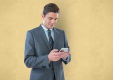 Geschäftsmann unter Verwendung des intelligenten Telefons gegen gelben Hintergrund Stockbild