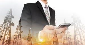 Geschäftsmann unter Verwendung des intelligenten Telefons mit panoramischem Stadtbild und Telekommunikation der Doppelbelichtung  stockfotos