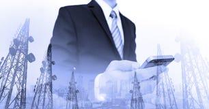 Geschäftsmann unter Verwendung des intelligenten Telefons mit panoramischer Stadt und Telekommunikation der Doppelbelichtung ragt stockbild
