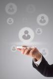 Geschäftsmann unter Verwendung des intelligenten Telefons, zum seines Teams mitzuteilen virtuell Stockbild