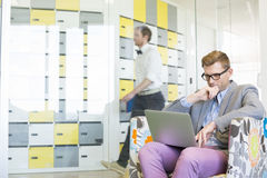 Geschäftsmann unter Verwendung des Laptops auf Lehnsessel mit dem Kollegen, der in Hintergrund im kreativen Büro geht Lizenzfreies Stockbild