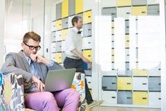 Geschäftsmann unter Verwendung des Laptops auf Lehnsessel mit dem Kollegen, der in Hintergrund im kreativen Büro geht Stockfotografie