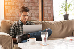 Geschäftsmann unter Verwendung des Laptops auf Sofa in der Kaffeestube Stockbilder