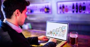 Geschäftsmann unter Verwendung des Laptops beim Sitzen in der Stange Stockbilder