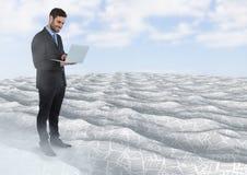 Geschäftsmann unter Verwendung des Laptops im Meer von Dokumenten unter Himmel bewölkt sich Stockbild