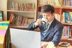 Geschäftsmann unter Verwendung des Laptops mit Tablette und Stift auf Holztisch Lizenzfreie Stockbilder