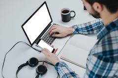 Geschäftsmann unter Verwendung des Laptops und des Telefons mit leerem Bildschirm Stockbilder