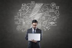 Geschäftsmann unter Verwendung des Laptops vor Tafel mit Ikonen Lizenzfreie Stockfotos