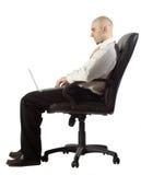 Geschäftsmann unter Verwendung des Laptops, während Sie gesetzt werden stockbilder