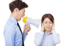 Geschäftsmann unter Verwendung des Megaphons, zum an der Geschäftsfrau zu schreien stockbild