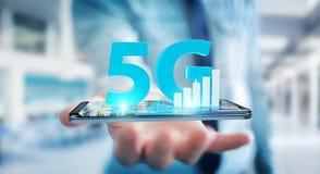 Geschäftsmann unter Verwendung des Netzes 5G mit Wiedergabe des Handys 3D Lizenzfreie Stockfotos