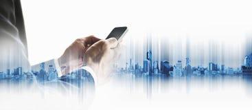 Geschäftsmann unter Verwendung des Smartphone mit Doppelbelichtungsstadthintergrund, Geschäftskommunikationstechnologiekonzept stockbild