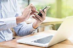 Geschäftsmann unter Verwendung des Smartphone und der Laptop-Computers Stockfotos