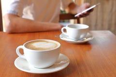 Geschäftsmann unter Verwendung des Social Media durch Handy im Café mit der Schale des Lattekaffees auf dem Tisch mit Kopienraum lizenzfreies stockfoto