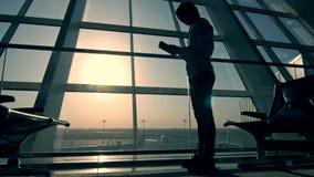 Geschäftsmann unter Verwendung des Tablet-Computers am Flughafen Schattenbild eines Mannreisenden mit Rucksack Geschäft und Reise stock video