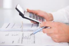 Geschäftsmann unter Verwendung des Taschenrechners im Büro Stockfoto