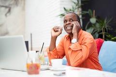 Geschäftsmann unter Verwendung des Telefons beim Arbeiten an Laptop in einem Restaurant Stockfotos