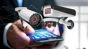 Geschäftsmann unter Verwendung eines Smartphone mit einem Überwachungskamerasystem und Lizenzfreies Stockfoto