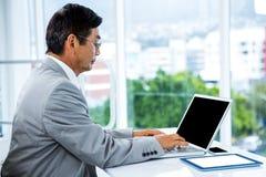Geschäftsmann unter Verwendung seines Computers Stockfoto