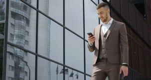 Geschäftsmann unter Verwendung seines intelligenten Telefons Hübscher junger Mann, der auf dem Smartphonelächeln überzeugt in Ver stock video footage