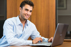 Geschäftsmann unter Verwendung seines Laptops im Büro stockfotos