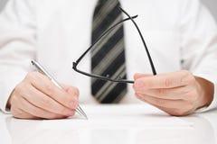 Geschäftsmann unterzeichnet Vereinbarung mit Gläsern in der Hand Lizenzfreies Stockfoto