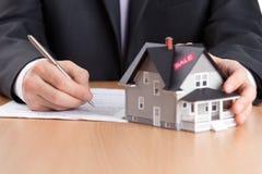 Geschäftsmann unterzeichnet Vertrag hinter Haus architectu lizenzfreie stockfotografie