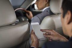Geschäftsmann Use Mobile Inside ein Auto stockfotos