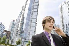 Geschäftsmann-Using Cellphone Against-Gebäude stockfotografie