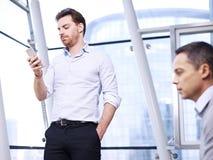 Geschäftsmann-Using Cellphone In-Büro Stockbilder
