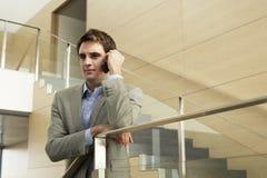 Geschäftsmann Using Cellphone While, das auf Glasgeländer sich lehnt stockbild