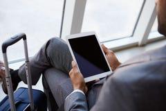 Geschäftsmann Using Digital Tablet im Flughafen-Abfahrt-Aufenthaltsraum lizenzfreie stockfotos