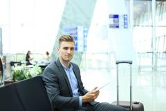 Geschäftsmann Using Digital Tablet im Flughafen-Abfahrt-Aufenthaltsraum stockbilder