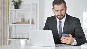 Geschäftsmann Using Smartphone und Laptop bei der Arbeit stock video