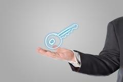Geschäftsmann, Verkäufer, Schlüsselsymbol in der Hand Stockfotografie