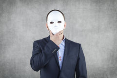 Geschäftsmann versteckt hinter der Maske Stockfotografie