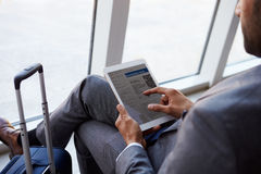 Geschäftsmann Viewing Boarding Pass im Flughafen-Aufenthaltsraum lizenzfreie stockbilder