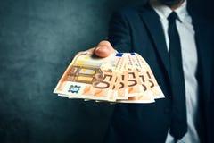 Geschäftsmann von Angebotgelddarlehen der Bank in den Eurobanknoten Stockbilder