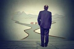 Geschäftsmann vor zwei Straßen die Entscheidung denkend Stockbilder