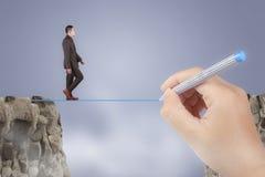 Geschäftsmann Walks Trough Obstacle Gap mithilfe durch großen Mentor-Führer stockfoto