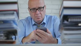 Geschäftsmann Wearing Eyeglasses Text unter Verwendung des Mobiltelefons im Büro lizenzfreies stockbild