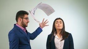Geschäftsmann wird die Papiere in einem Kollegen werfen, der bescheiden oben seine Augen schaut Lizenzfreies Stockbild