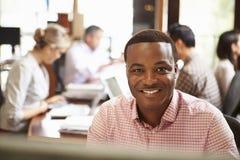 Geschäftsmann Working At Desk mit Sitzung im Hintergrund Stockfotografie
