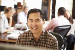 Geschäftsmann Working At Desk mit Sitzung im Hintergrund Lizenzfreies Stockfoto