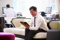 Geschäftsmann-Working On Digital-Tablet in der Hotel-Lobby Lizenzfreie Stockfotos