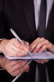 Geschäftsmann Writing On Paper mit Stift Lizenzfreie Stockbilder