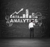 Geschäftsmann zeichnet Analytiklösung auf der schwarzen Wand lizenzfreie stockbilder
